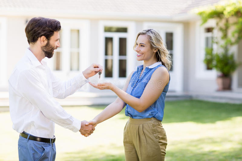 Real estate agent giving keys to woman stock image