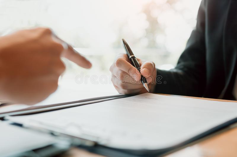 Real estate agent hand showing customer where to writing sign a contract of house or mortgage papers.  stock images