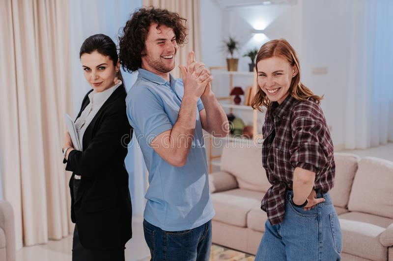 Real estate agent and her clients in front of the camera in amazing large apartment looking straight to the camera and stock images