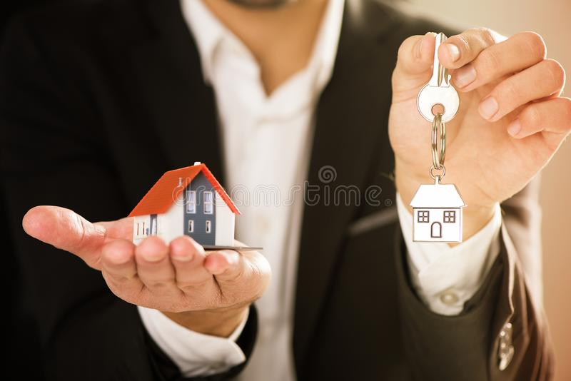 Real Estate agent hoding house model and house key. Buy new house concept royalty free stock images
