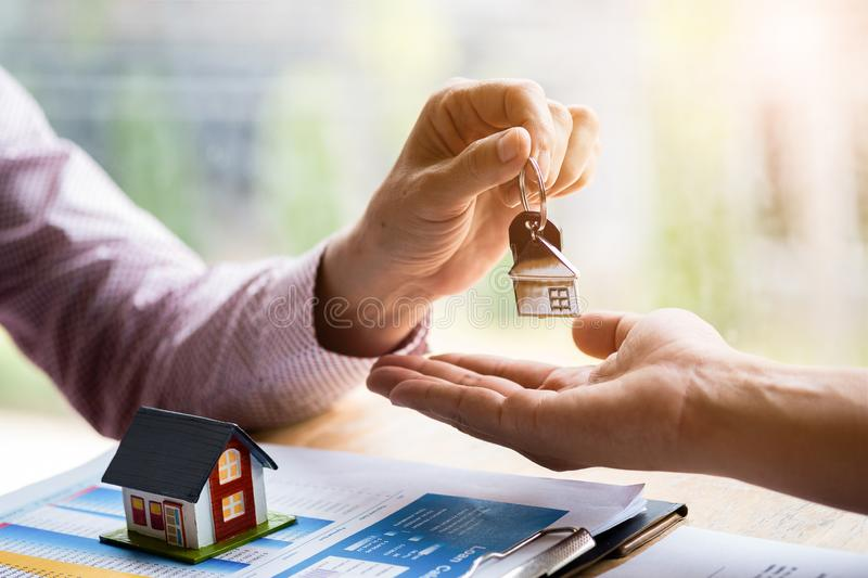 Real estate agent holding filing keys to customer after signing rental lease contract of sale purchase agreement.  royalty free stock images