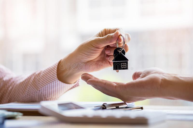Real estate agent holding filing keys to customer after signing rental lease contract of sale purchase agreement.  stock image