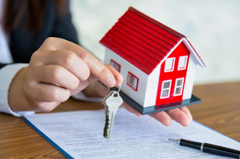 Real estate agent holding house key to his client after signing contract agreement in office,concept for real estate, renting. Property stock photography