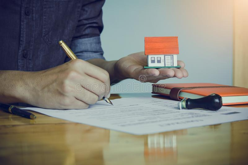 Real estate agent holding house model in hand and signing contract,signing of modest agreements form in office. Concept real estate,moving home or renting stock image
