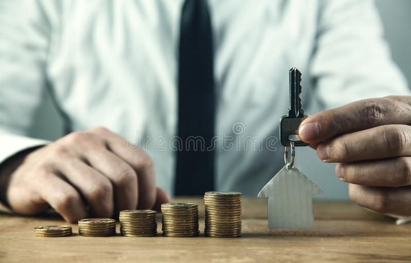Real estate agent holding house model and key. Saving money for buying real estate property stock photos