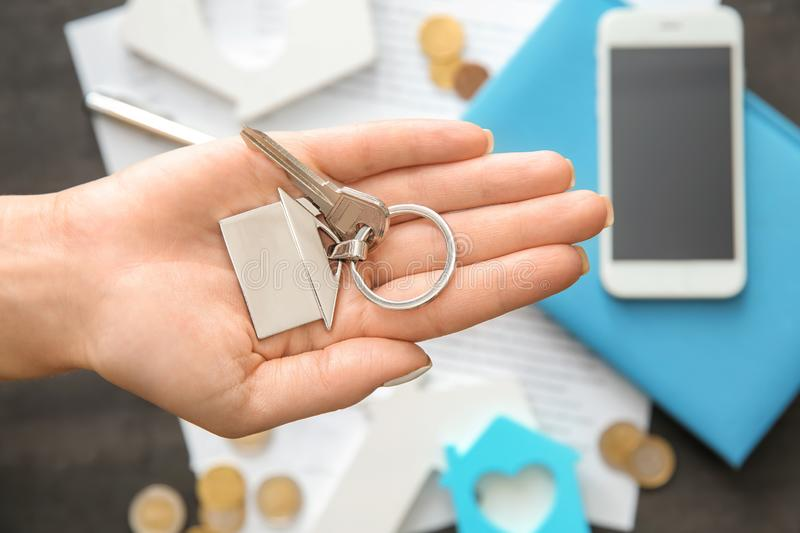 Real estate agent holding key with trinket in shape of house. Mortgage concept stock photography