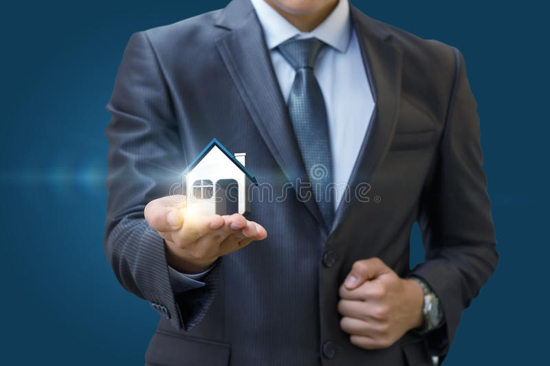 Real estate agent holding a model house in hand . Real estate agent holding a model house in hand on blue background stock photography