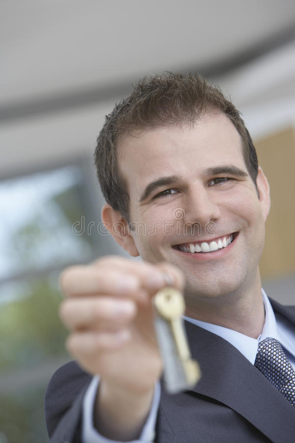 Real Estate Agent Holding Out House Key royalty free stock image