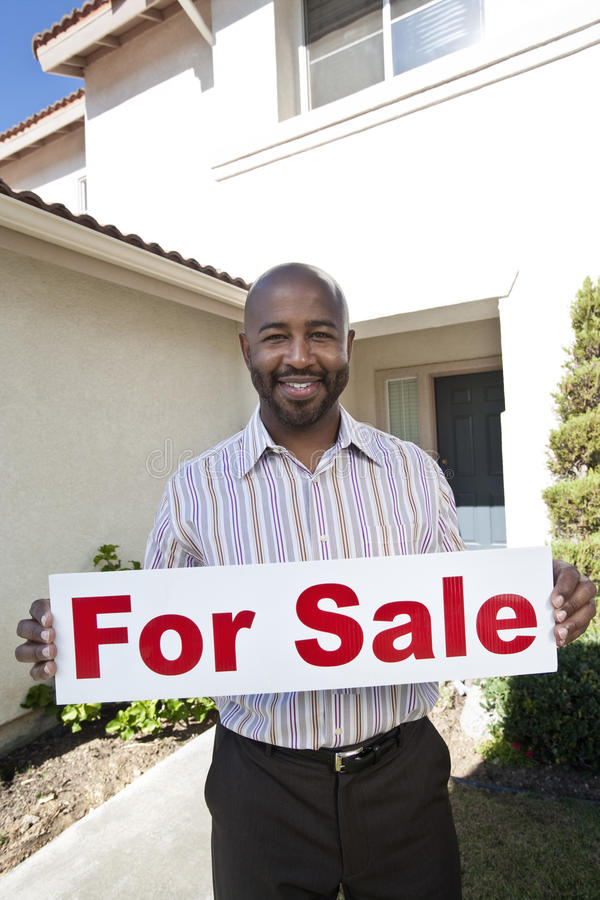Real Estate Agent Holding 'For Sale' Sign. Portrait of a happy estate agent holding 'For Sale' sign outside house royalty free stock photos