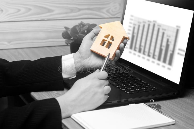 Real estate agent holds a house model, signs fills documents sitting behind laptop. sales schedule. sale apartments for rent. sele royalty free stock images