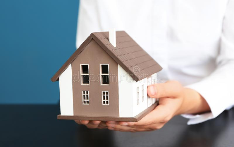 Real estate agent with house model at dark table, closeup stock photography