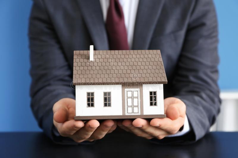 Real estate agent with house model at dark table. Mortgage concept stock photos