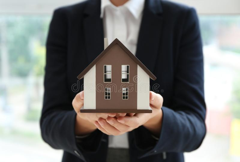 Real estate agent with house model indoors royalty free stock photography