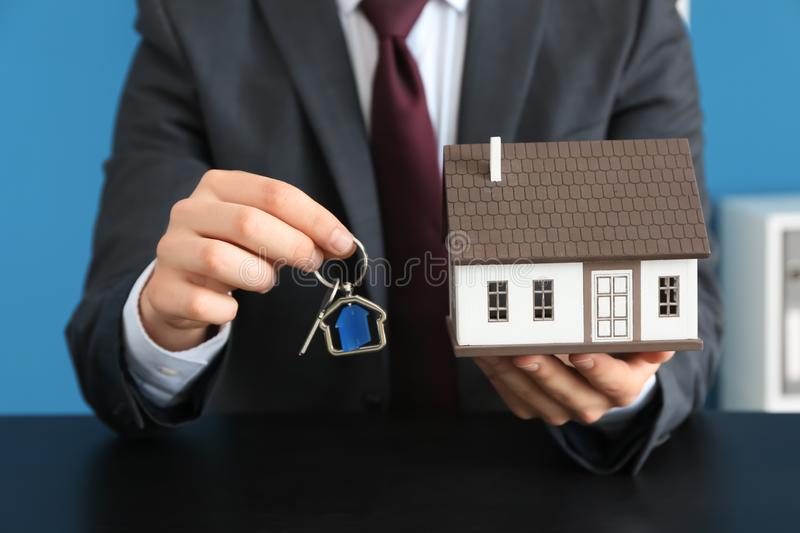 Real estate agent with house model and key at dark table. Mortgage concept stock images