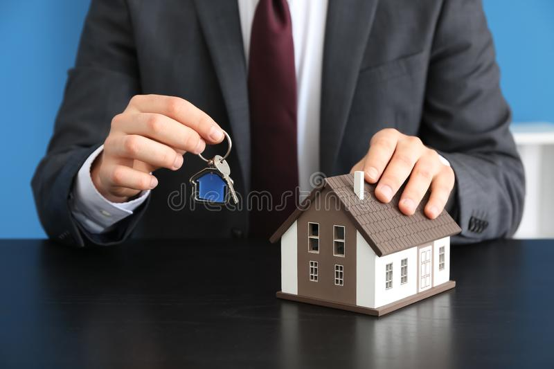 Real estate agent with house model and key at dark table. Mortgage concept royalty free stock photos