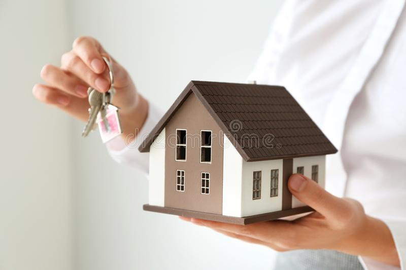 Real estate agent with house model and key on light background, closeup royalty free stock photography