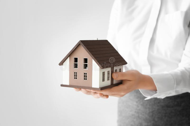 Real estate agent with house model on light background stock photography
