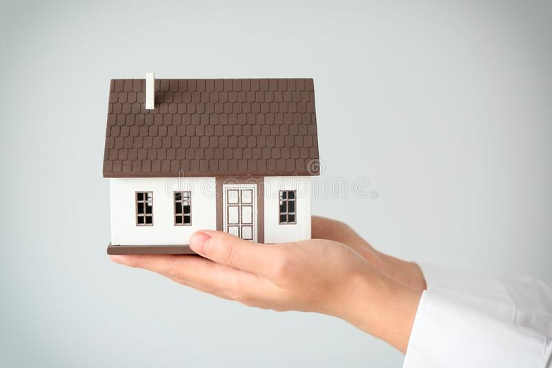 Real estate agent with house model on light background, closeup royalty free stock photography
