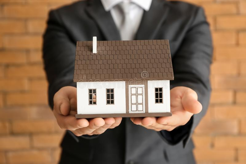 Real estate agent with house model near brick wall, closeup. Mortgage concept royalty free stock photography