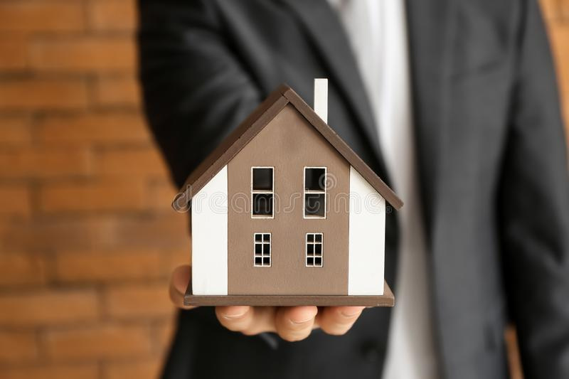 Real estate agent with house model near brick wall, closeup. Mortgage concept royalty free stock image