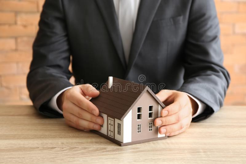 Real estate agent with house model at wooden table royalty free stock images
