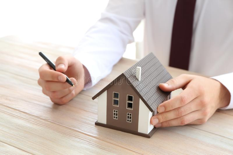 Real estate agent with house model at wooden table. Mortgage concept stock photography