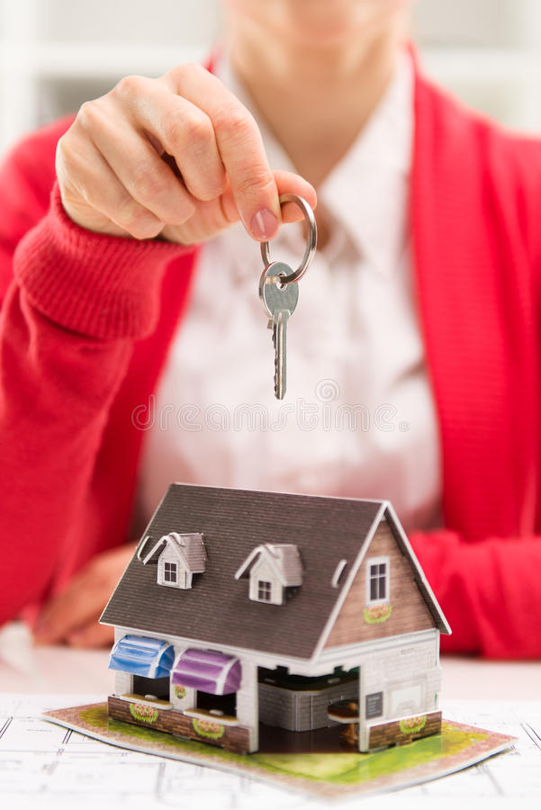 Real estate agent with key. Real estate agreement. Client buying new house in broker office. Close-up of female realtor's hand with key ring. Shallow depth of royalty free stock image