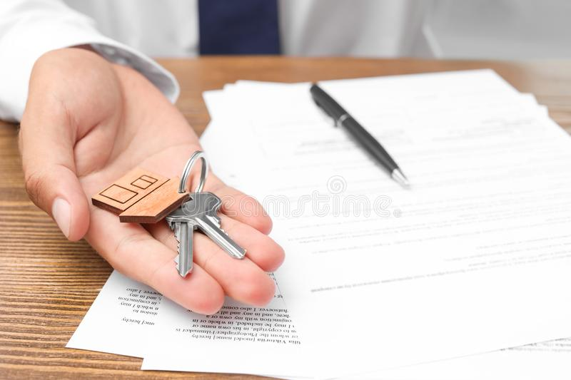 Real estate agent with keys and documents. At table stock image