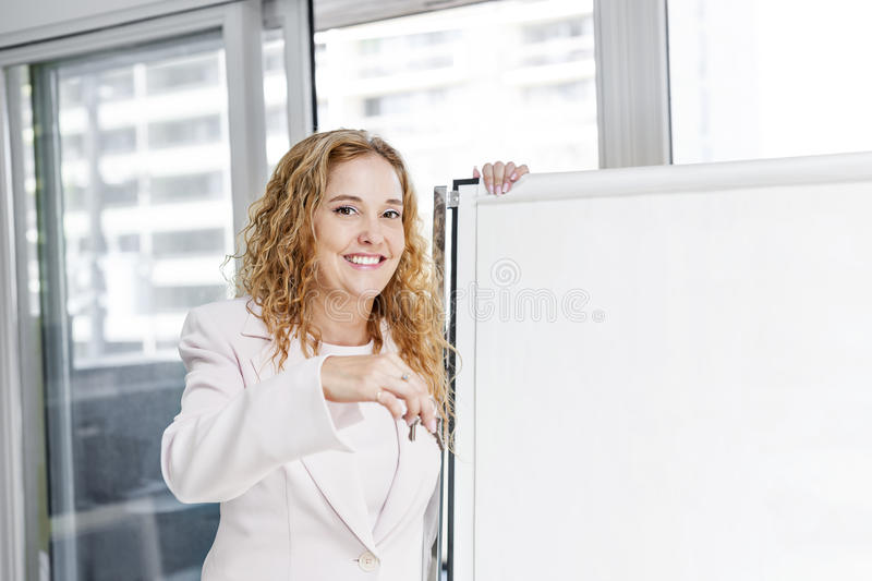 Real estate agent with keys and flip chart. Smiling female real estate agent offering keys standing with blank flip chart stock photos