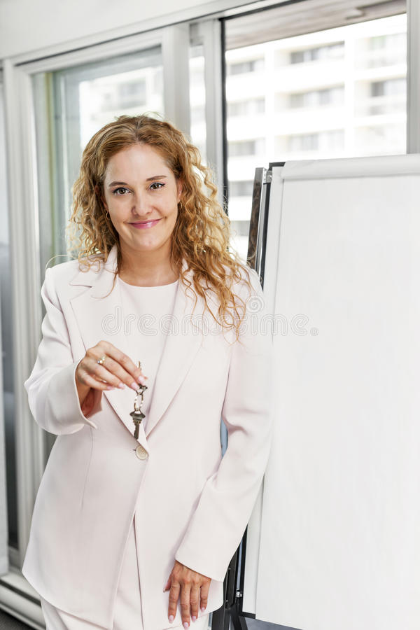 Real estate agent with keys and flip chart stock photography