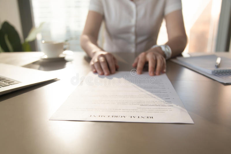 Real estate agent offers client to sign rental agreement, closeu. Real estate agent offers to read rental agreement to client for rent house apartment, realtor stock photo