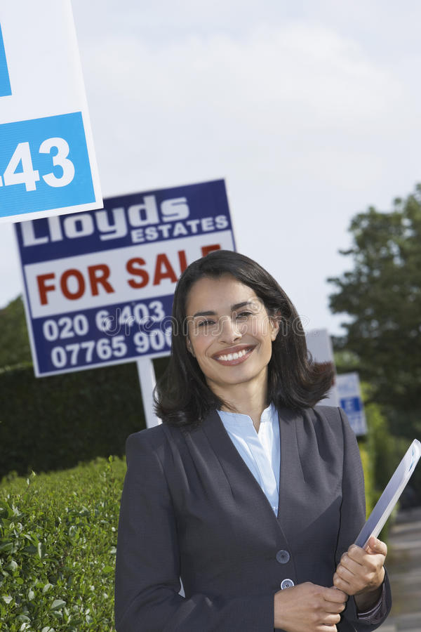 real estate agent by for sale sign outside house stock photo