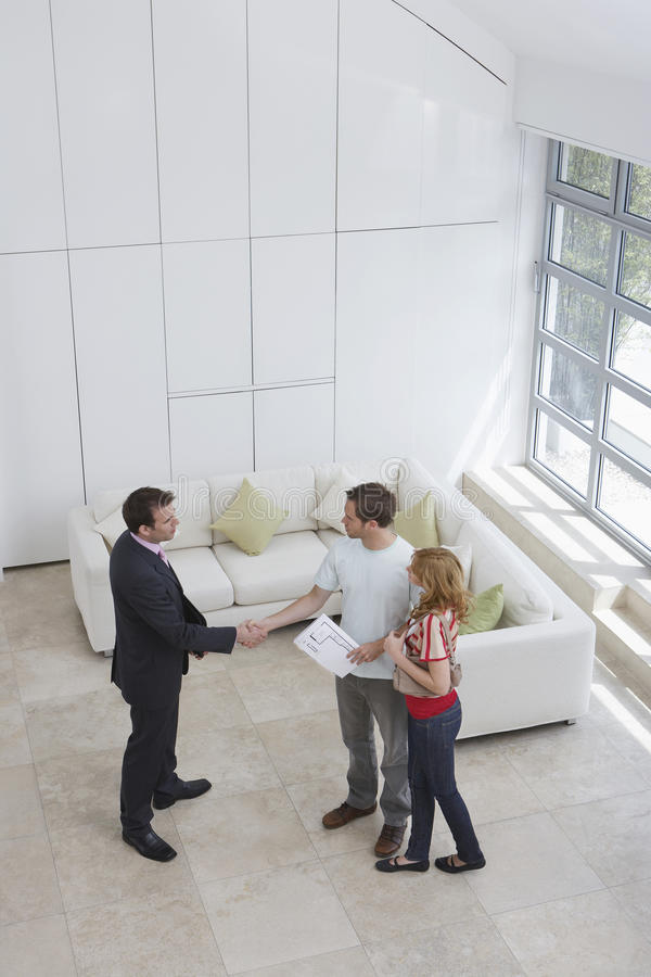 Real Estate Agent Shaking Hands With Man By Woman In New Home stock photos