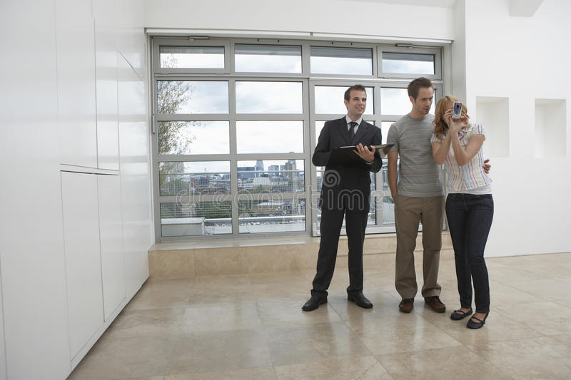 Real Estate Agent Showing Couple New Apartment royalty free stock image