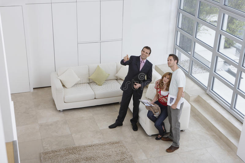 Real Estate Agent Showing Couple New Home. Elevated full length view of a male real estate agent showing couple new home royalty free stock image
