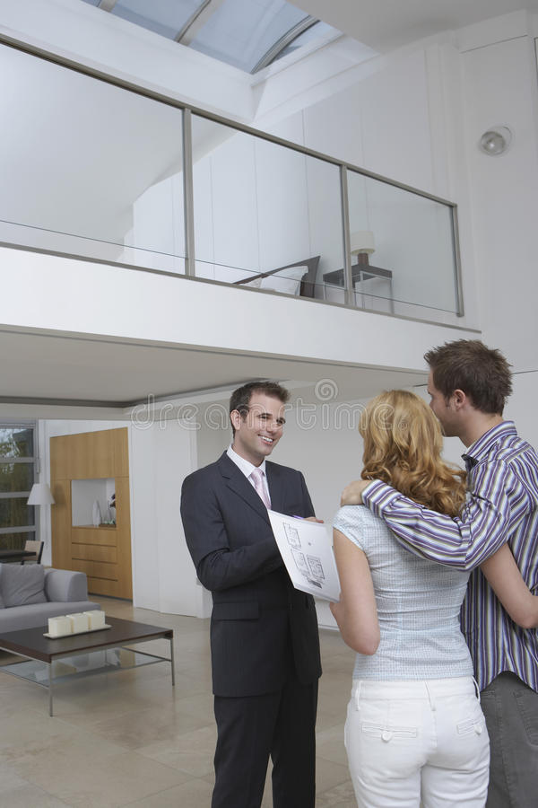 Real Estate Agent Showing Couple New Home. Friendly male real estate agent showing couple new home stock image