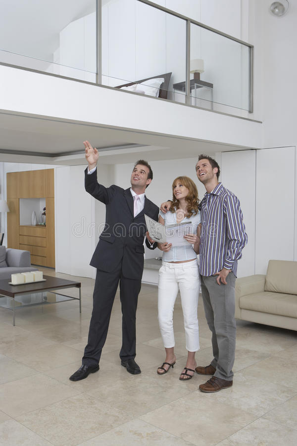 Real Estate Agent Showing Couple New Home. Full length of a male real estate agent showing couple new home royalty free stock photos