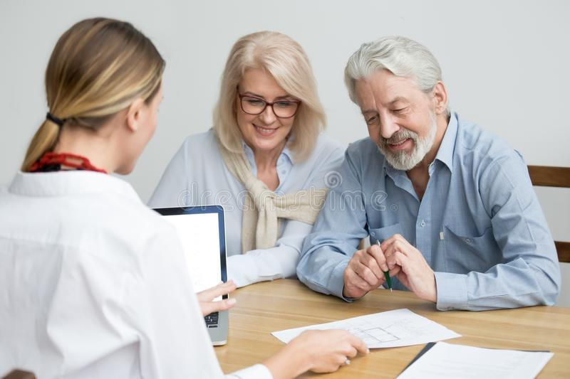 Real estate agent showing house plan consulting aged senior coup. Real estate agent showing house plan to aged couple, realtor making property for sale offer to royalty free stock photos