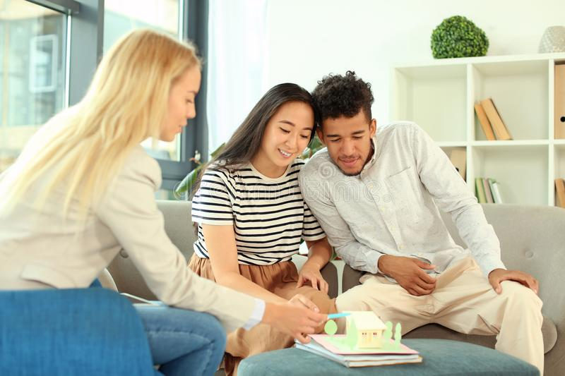 Real estate agent showing model of house to clients in her office stock images