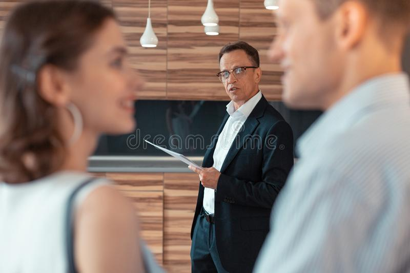 Real estate agent speaking to couple telling about house stock photography