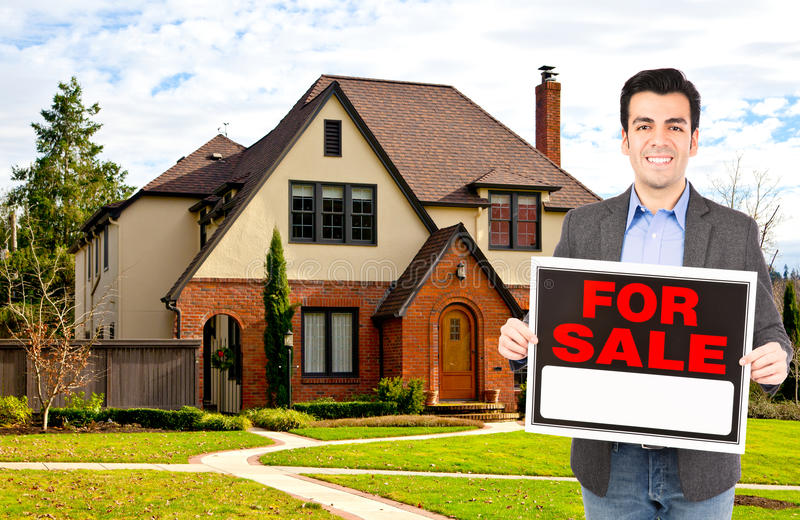 Real estate agent standing outside house. Real estate agent at work standing outside house holding for sale sign royalty free stock image