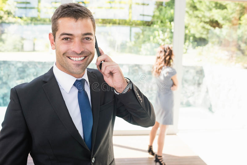 Real-estate agent talking on the mobile phone. And client looking at the apartment royalty free stock photo