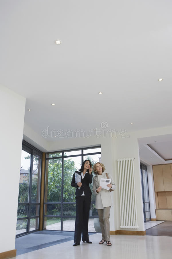 Real Estate Agent And Woman Observing New Property. Full length of a female real estate agent and woman observing new property stock photos