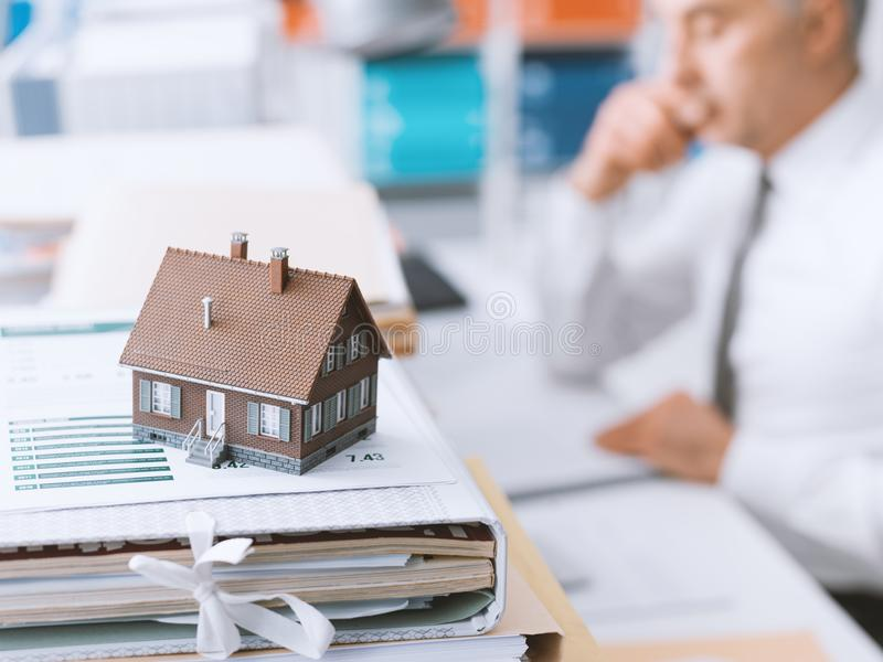 Real estate, mortgage loans and paperwork. Real estate agent working in the office and piles of paperwork, model house on the foreground and mortgage loan royalty free stock photos
