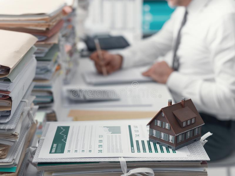 Real estate, mortgage loans and paperwork. Real estate agent working in the office and piles of paperwork, model house on the foreground and mortgage loan royalty free stock photography
