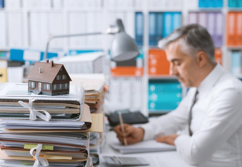 Real estate, mortgage loans and paperwork. Real estate agent working in the office and piles of paperwork, model house on the foreground and mortgage loan stock photography
