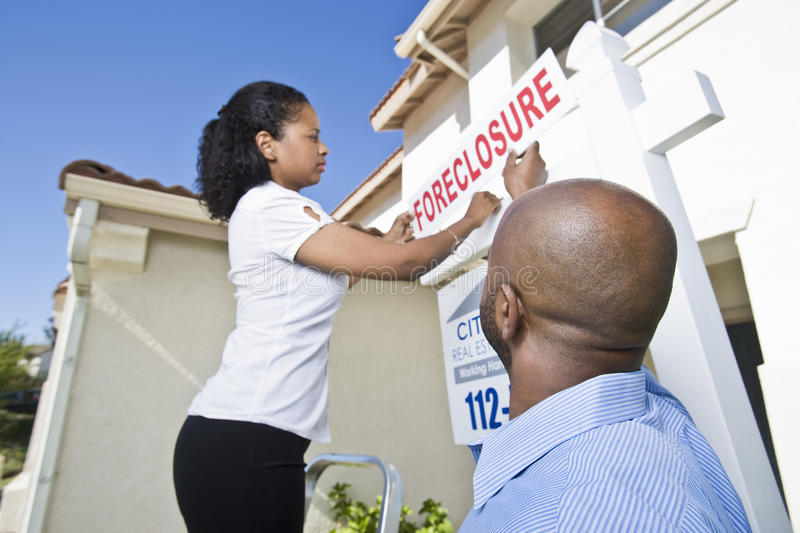 Real Estate Agents Putting ~For Sale~ Notice Outside House. Two multiethnic real estate agents putting ~For Sale~ notice outside house royalty free stock photo