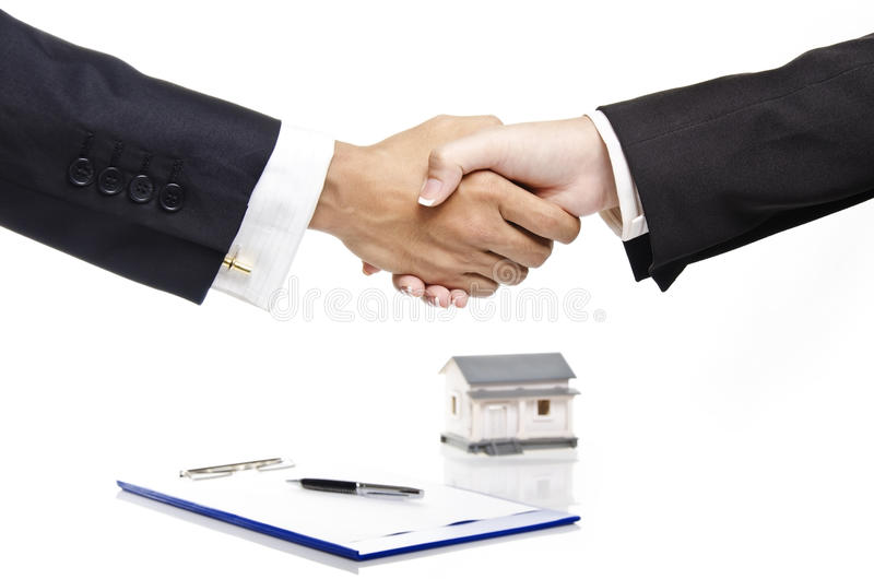 Real estate agreement. Handshaking of real estate agent over contract paper royalty free stock photos