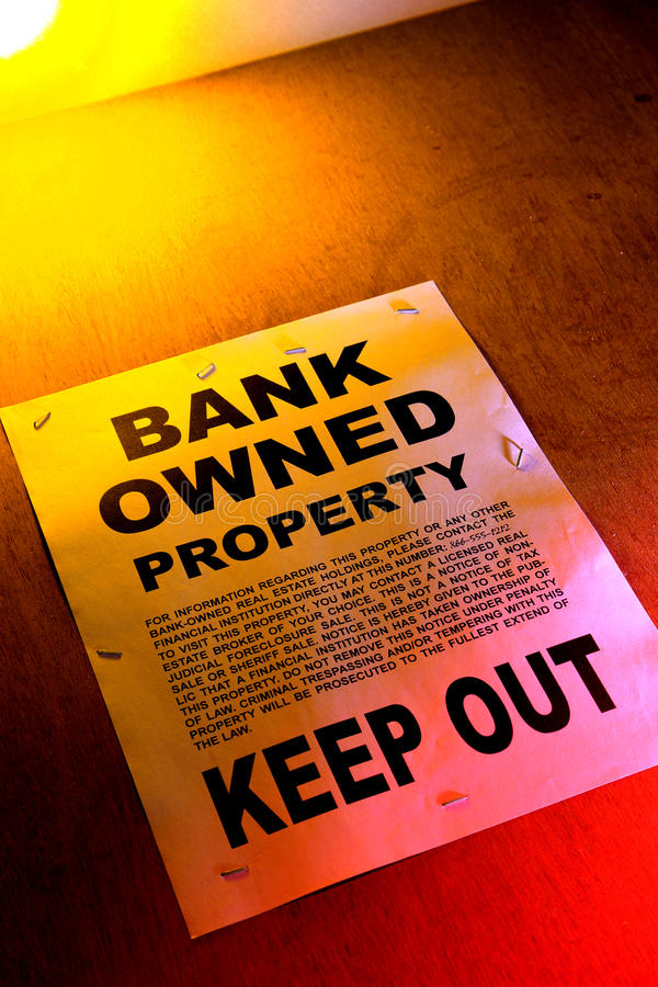 Real Estate Bank Owned Sign Poster on Building. Grunge Real estate lender bank owned keep out sign notice posted on a boarded up foreclosed building in stock photo