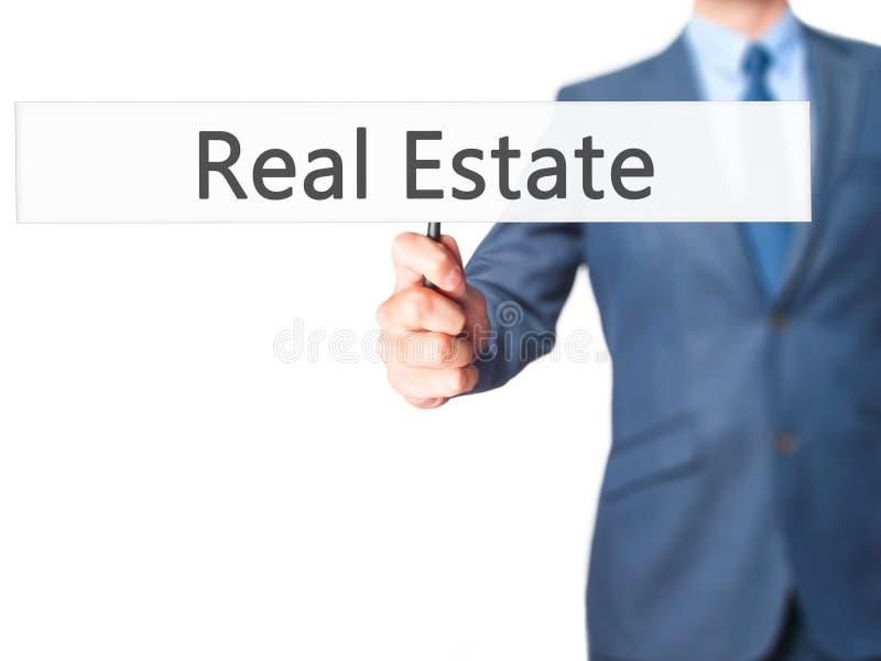Real Estate - biznesmen ręki mienia znak obrazy stock